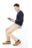 Sit and use pad. Handsome Asian guy sit and use pad, full length portrait isolated on white background Royalty Free Stock Photography