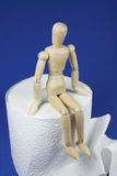 Sit and wait. Wooden figure sit on toilet paper Royalty Free Stock Photos