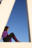 Sit and wait. Young woman sitting in the triangle of a lifeguard tower Royalty Free Stock Images
