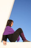 Sit and wait. Young woman sitting in the triangle of a lifeguard tower Stock Image
