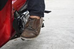 Sit on your motorcycle and Start the engine with foot start rod or Kick starter stock image