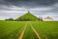Site commémoratif du monticule du lion célèbre au champ de bataille de Waterloo avec les nuages foncés, Belgique photographie stock libre de droits