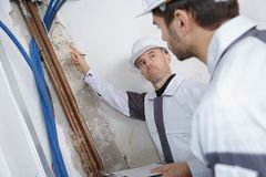 Site inspector inspecting wall. Site inspector inspecting the wall Royalty Free Stock Images