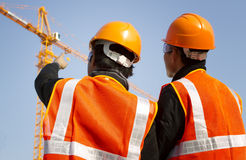 Construction workers with crane in background Stock Photography