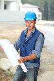 Site manager standing with plan Royalty Free Stock Photo