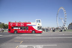 Site seeing bus drives over westminster bridge with london eye i Royalty Free Stock Photo