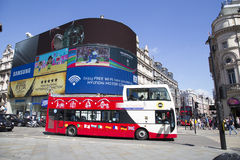 Site seeing bus passing big screen in piccadilly circus Royalty Free Stock Photography