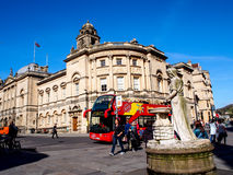 Site seeing bus wait for tourists at historical site Roman Bath, UK Royalty Free Stock Image