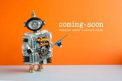 Site sob a construção que vem logo página Robô do brinquedo com chave de fenda e a ampola Assoalho cinzento da parede alaranjada fotografia de stock