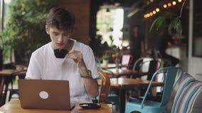 Site Web et causerie surfante de jeune homme, indépendant et blogger travaillant en tant que concepteur d'intérieur, et café pota banque de vidéos