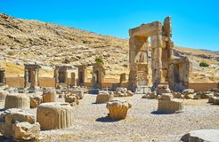 Sites of ancient Persia. The stone ruins of Hundred Columns Hall of Persepolis with the rocky slope of Rahmet Mount on the background, Iran Royalty Free Stock Image