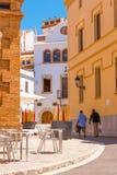 SITGES, CATALUNYA, ИСПАНИЯ - 20-ОЕ ИЮНЯ 2017: 2 люд идут через историческую часть города Скопируйте космос для текста вертикально Стоковое Изображение