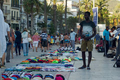 Sitges, Spain - 21 August 2016: Africans sell goods on promenade. Sitges, Spain - 21 August 2016: Tourists walking pass vendors that sell bags, purses and stock photos