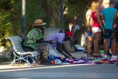 Sitges, Spanien - 21. August 2016: Afrikaner bereiten vor sich, gefälschte Waren auf Promenade von Sitges zu verkaufen Lizenzfreie Stockbilder