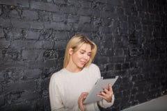 Siti femminili allegri dello sviluppatore facendo uso della compressa digitale portatile Libro elettronico della lettura dello st Fotografie Stock