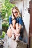 sitiing在墙壁附近的牛仔裤和起动的亭亭玉立的女孩 免版税库存照片