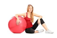 sitiing在楼层上的新女性运动员在pilates球旁边 免版税库存照片