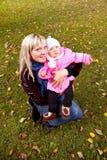年轻sitiing在草的母亲和小孩在秋天公园 免版税库存图片