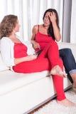 sitiing在长沙发和谈的两名可爱的妇女 库存图片