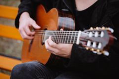 Siting bench and play guitar Stock Image