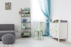 Sitio acogedor con el sofá gris y el aparador blanco Imágenes de archivo libres de regalías