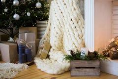 Sitio acogedor del día de fiesta hermoso con el árbol de navidad, la chimenea y la manta blanca Imagen de archivo libre de regalías