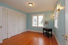 Sitio azul con el suelo de la cereza y las puertas blancas del armario Fotografía de archivo