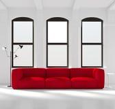 Sitio blanco con un sofá rojo Fotos de archivo