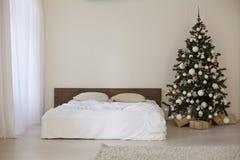 Sitio blanco de la decoración con los regalos de la Navidad del Año Nuevo de la cama Foto de archivo