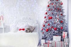Sitio brillante acogedor con una cama y un árbol de navidad imágenes de archivo libres de regalías