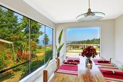Sitio brillante con el sistema de la mesa de comedor y la opinión hermosa de la ventana Foto de archivo