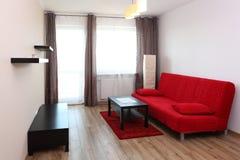 Sitio con el sofá rojo Imagenes de archivo