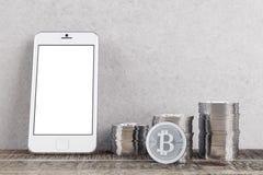 Sitio con los bitcoins y el teléfono Imágenes de archivo libres de regalías