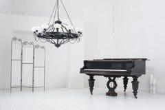 Sitio con un piano, una pantalla plegable y una lámpara foto de archivo libre de regalías