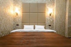 Sitio con una cama matrimonial, mesita de noche, y una puerta blanca, paredes grises y un suelo laminado En cada lado de la cama  fotografía de archivo libre de regalías