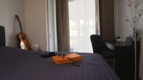 Sitio de estudiantes vacío con la tabla, la cama y la guitarra, apartamento cómodo, hogar almacen de video