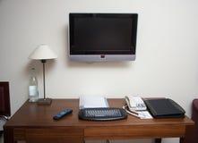 Sitio de estudio con la lámpara del teléfono del teclado del escritorio y el aparato de TV del lcd Fotos de archivo libres de regalías