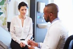 Sitio de hospital femenino del paciente y del doctor Have Consultation In Foto de archivo libre de regalías