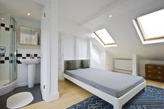 Sitio de la cama con el cuarto de baño de la habitación del en Fotos de archivo