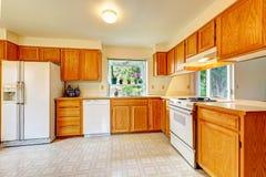 Sitio de la cocina con los gabinetes del arce y los dispositivos blancos Imagen de archivo