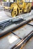 Sitio de la construcción de carreteras con el carril de la tranvía y el rodillo del tambor de acero Foto de archivo libre de regalías