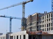 Sitio de la construcción de edificios concretos con las grúas en cielo azul Fotos de archivo libres de regalías