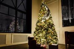 Sitio de la decoración del ` s del Año Nuevo con una ventana enorme del desván Árbol de navidad elegante mágico hermoso Fotos de archivo