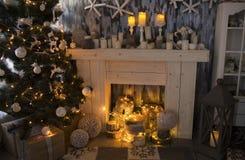 Sitio de la Navidad con la chimenea, presentes debajo del árbol de abeto adornado Imagen de archivo libre de regalías