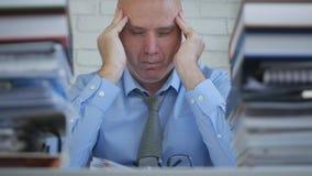 Sitio de la oficina de Working Late In del empresario que sufre dolor de cabeza grande foto de archivo