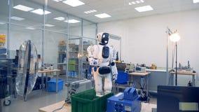 Sitio de oficina de ingeniería con un robot que levanta su mano y que dobla los fingeres metrajes