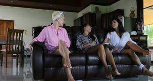Sitio de Sit On Couch Talking Living de las muchachas en el interior moderno del apartamento, mañana de la comunicación del grupo almacen de video