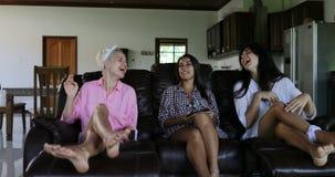 Sitio de Sit On Couch Talking Living de las muchachas en el interior moderno del apartamento, mañana de la comunicación del grupo metrajes