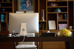 Sitio de trabajo con la tabla y detrás de la vista de la mesa del ordenador imágenes de archivo libres de regalías