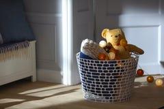 Sitio del bebé con la cesta del juguete y el oso de peluche Imágenes de archivo libres de regalías